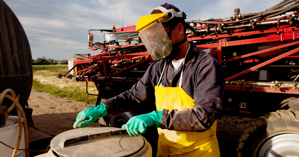 using proper safety equipment to fill sprayer with chemical and water