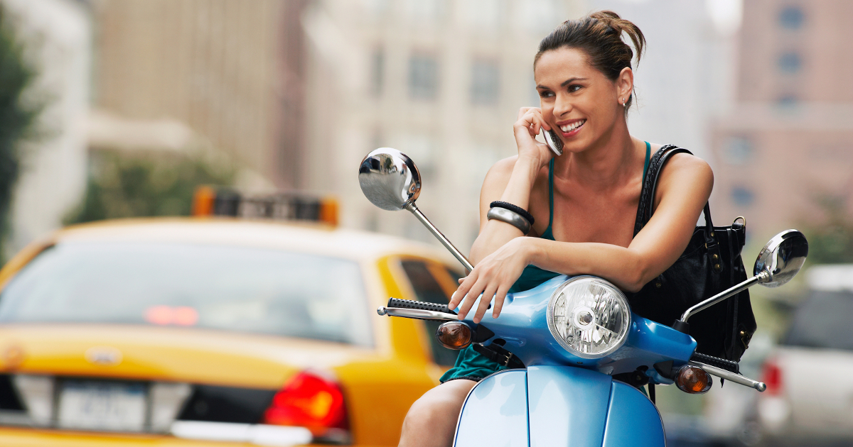 woman talking on cell phone on a scooter