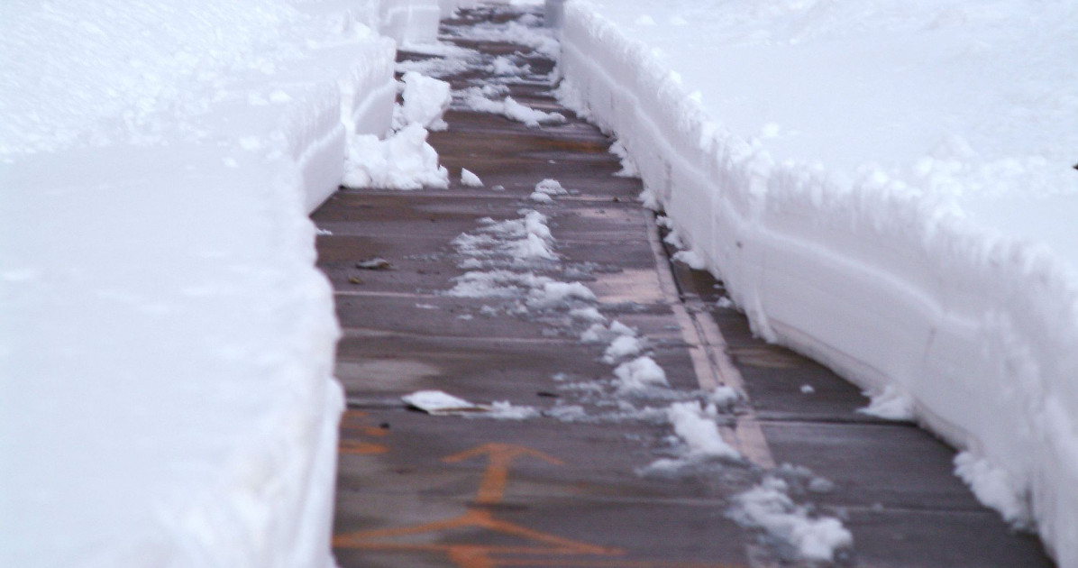 Icey sidewalk with snow drifts on each side